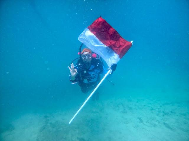Underwater flag hoisting ceremony at Tanjung Putus, Lampung, Indonesia