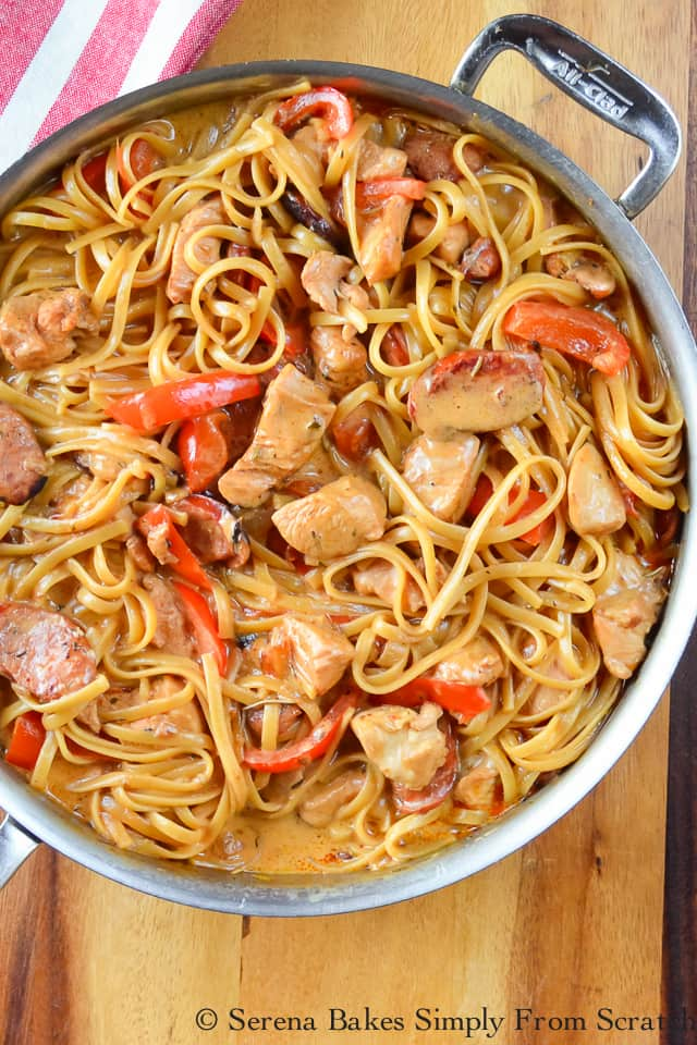 One Pot Cajun Chicken Pasta in a large skillet with a red and white stripped cloth in the upper left corner and placed on top of a wood cutting board.