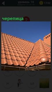 На крыше дома лежит коричневая черепица, уложенная волнами