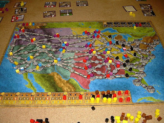 The game of Power Grid in the course of a four player game. The board represents a map of the continental United States with various cities connected by network lines. Wooden house tokens in the various players' colours have been placed on many of the cities. Along the bottom of the board are black, brown, orange, and yellow tokens representing the various resources. Cards and more tokens lie around the board on the table.