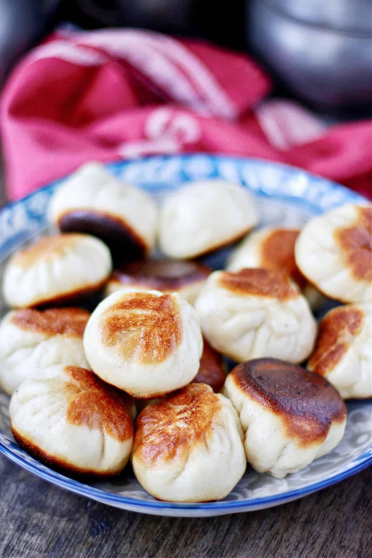 Pan Fried Pork and Scallion Buns (Shēng Jiān Bāo)  in a bowl.