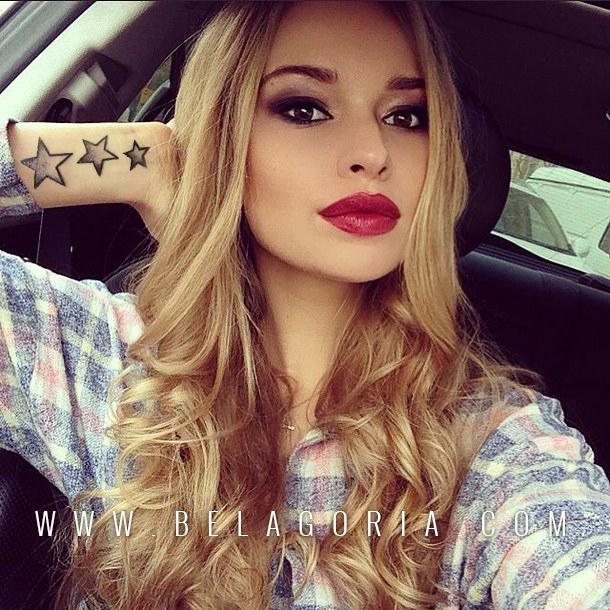Chica rubia posando en su automóvil, vemos que lleva un tattoo en la muñeca, el tatuaje de 3 estrellas