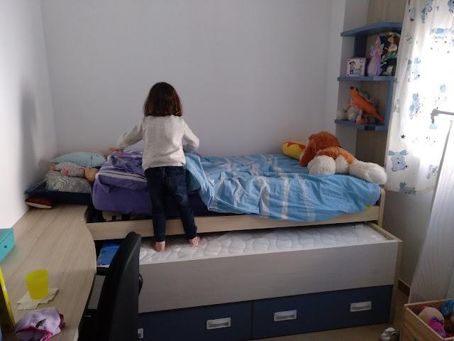Mi peque montada en la cama que está debajo de la suya (es una cama compacta) para poder llegar a la cama de arriba.