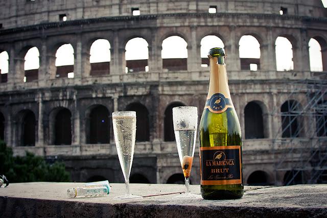 Taças e garrafa de champanhe com o Coliseu de fundo