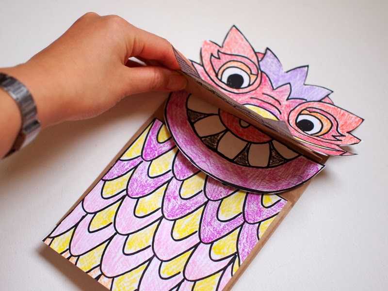 Glue on all the dragon pieces to your paper bag