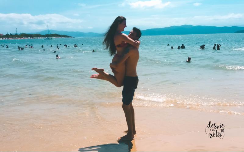 Casal se abraçando em frente ao mar