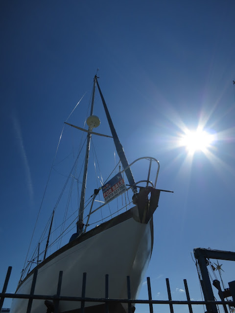 Looking up at a sailing boat with a for sale sign against a blue sky and white sun