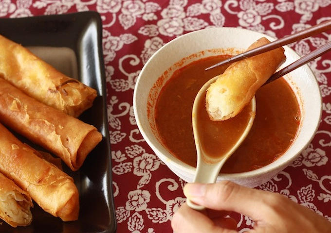 Asam laksa soup with deep fried spring rolls