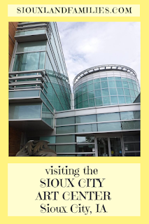 Photo of the front entrance of the Sioux City Art Center, a 3 story building including a rectangular brick section attached to a round glass and steel atrium