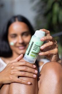 Mujer posando bajo el sol, con el bloqueador solar de Manzana verde, de la marca Seasons Love Your Skin.