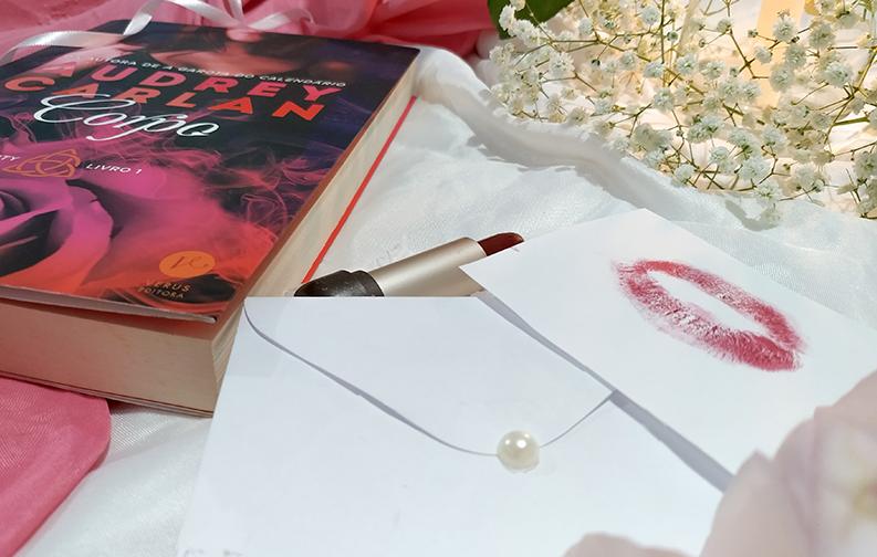 A imagem mostra o livro sobre um fundo branco. Ao lado direito do livro está localizado um batom vermelho, aberto, e um bilhete ao lado com uma marca de boca. Ao lado desses objetos, e em primeiro plano, está um pequeno envelope branco, com uma pérola servindo de fecho. A foto foi tirada na altura do batom, deixando o livro em segundo plano e destacando o batom e o bilhete