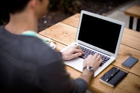 coat wearing man working on laptop on desk