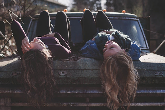 Two girls on the hood of a jeep, talking