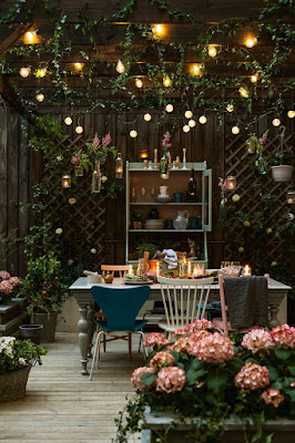 A wooden table with mismatched chairs in an arbor full of flowers and twinkly lights.