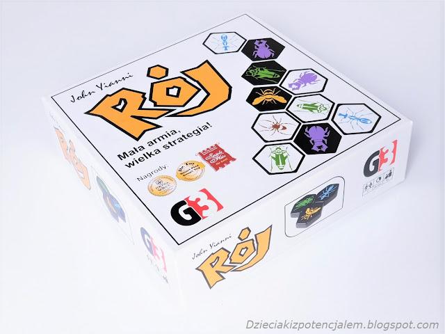 Pudełko od gry Rój kwadratowe w białym kolorze, na wierzchniej części narysowane są płytki do gry i symbole nagród i wyróżnień dla gry między innymi od od Mensa,