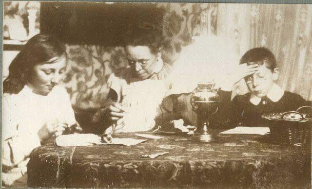 Seated at a table, with a oil lamp
