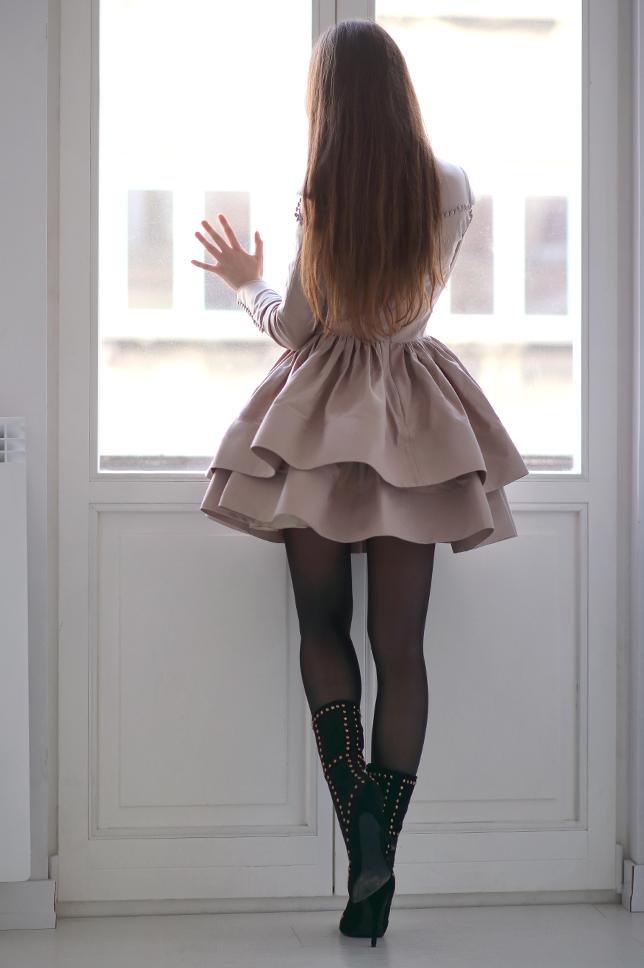 Beżowa rozkloszowana sukienka, czarne kryjące rajstopy i botki z ćwiekami