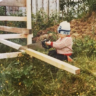 kuvastakuva vuodelta 83 pieni tyttö sahaa puuta kop-pipo päässä
