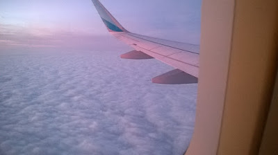 Wing of a plane over clouds, taken from an airplane window