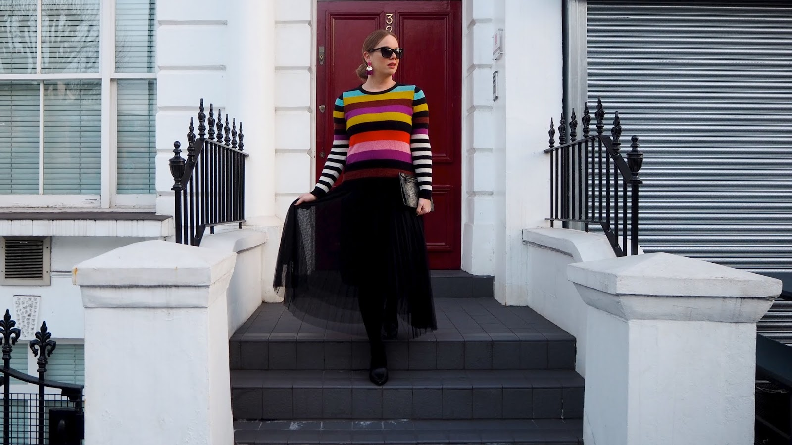 Rainbow stripe sweater, black pleated tulle skirt, black tights, black pointed toe shoes and snakeskin clutch