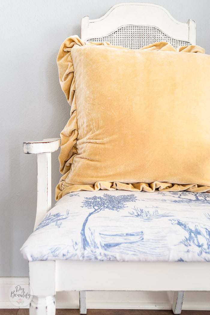 butter yellow velvet pillow with ruffles on painted vintage chair with blue toile seat cover