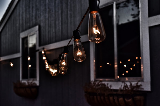Outdoor lighting hanging on a string along the side of a house