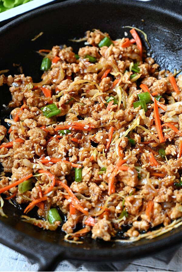 a pan with thai chicken for lettuce wraps and spring onion chopped