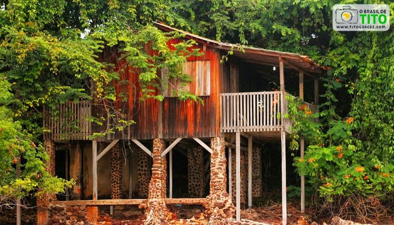 Casa de madeira envolta de árvores na praia da Caixa d'água, na vila do Algodoal, na ilha de Maiandeua, no Pará