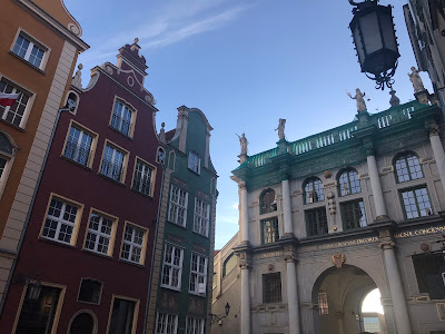 some coloured buildings in gdansk under a blue sky