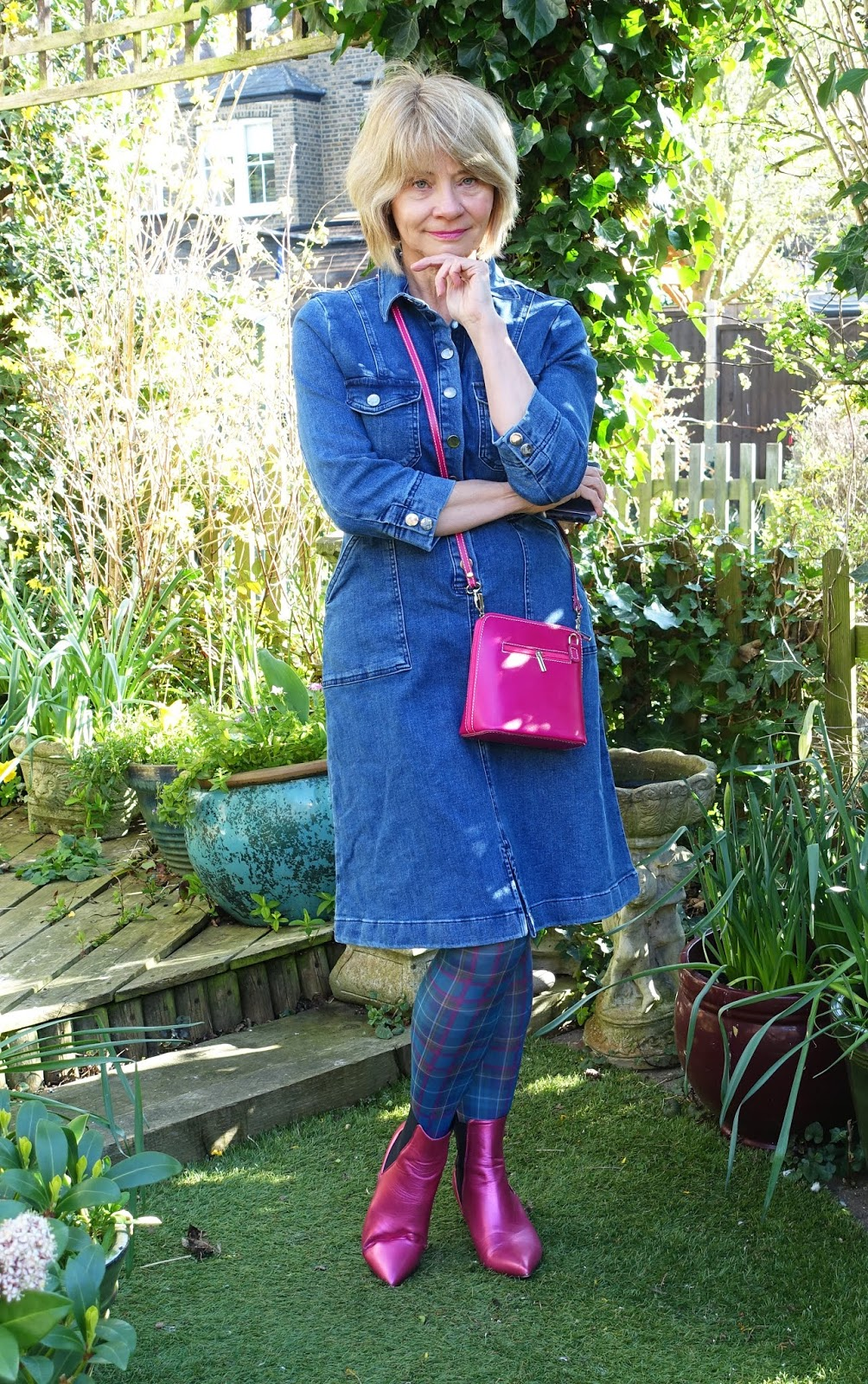 Over-50s style blogger in knee-length denim dress and fuchsia pink accessories
