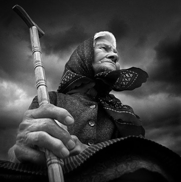 Black and White photo of an old lady, head covered, holding a cane. Shot drom below the subject looking into dark sky.Speak Your Mind and other stories of Grandmas and reason. marchmatron.com