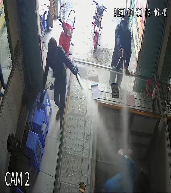 Hai tên cướp xịt hơi cay về phía chủ tiệm vàng.