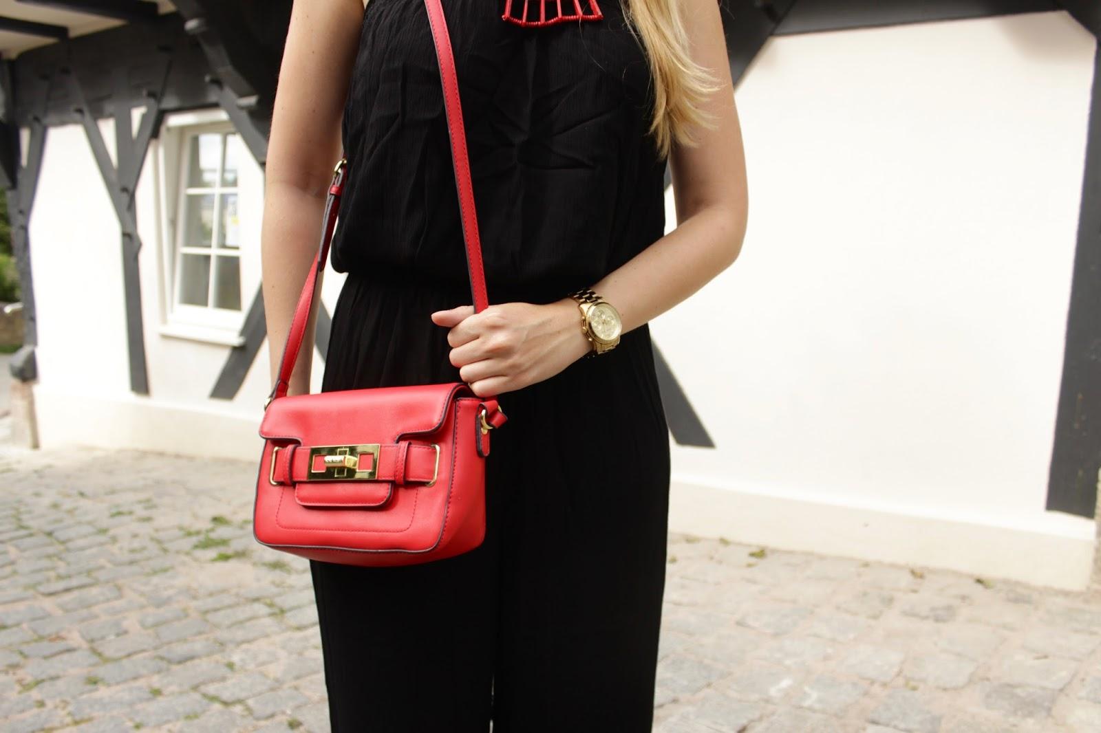 Fashion Outfit: schwarzer Jumpsuit mit roten Statement Accessoires