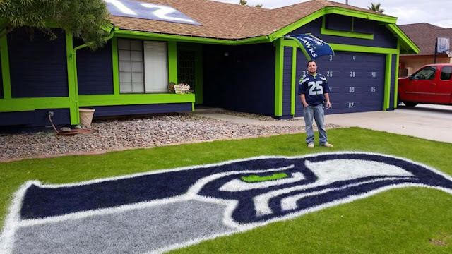 Man in a Seattle Seahawk jersey standing in from of a house painted in Seahawk blue with green trim. Seahawk emblem in the grass.