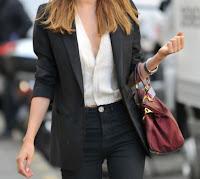 Mulher confiante e moderna: 5 dicas de estilo (mulher vestida com calças e blazer preto, blusa branca e mala de mão bordeaux)