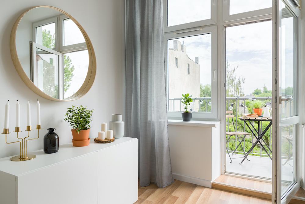 Recibidor con muebles blancos, espejo y acceso a la terraza