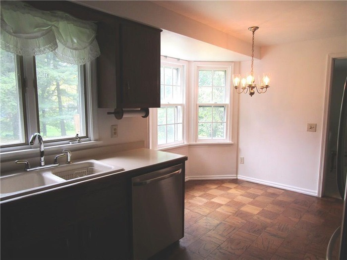 Dated colonial kitchen with parquet flooring and small breakfast nook
