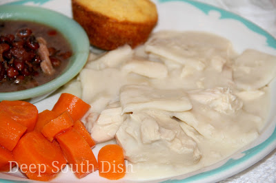 Homemade from scratch, Southern style chicken and dumplings, made from a whole chicken and rolled dumplings, and served here with steamed, buttered carrots, crowder peas and corn muffins.