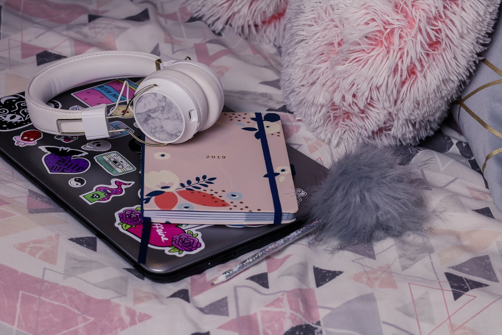 Close up photo of white headphones, a silver HP laptop and busy b diary that is pink sitting on a bed with geometric pink and great bed sheets.