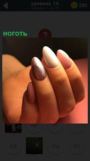 Женская рука с ногтями, на которых нанесен красивый маникюр