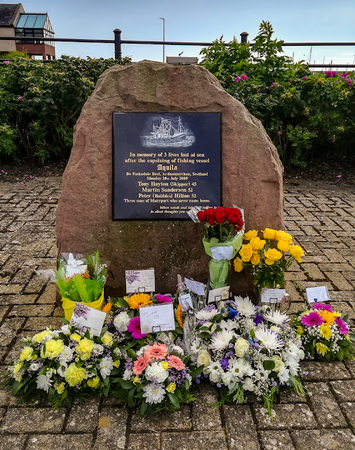 Photo of Aquila memorial and floral tributes in Maryport