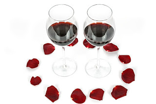 Two wine glasses filled with wine and surrounded by red rose petals