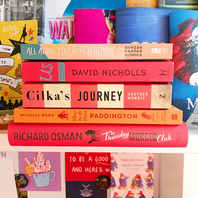 Stack of books on desk, background of musical prints and programs
