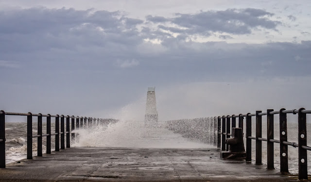 Photo of spray from the high waves being blown across the pier