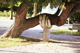 A tree being held up by a concrete support in the shape of a hand