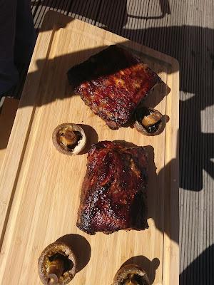 Zwei Stücke Dicke Rippe (gegrillt und mit Lasur überzogen) auf Brett zusammen mit vier großen gegrillten Champignons.