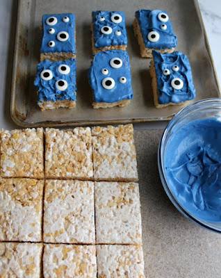 rice krispie treat squares by bowl of melted white chocolate dyed blue and tray of monster treats