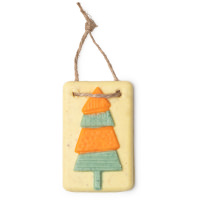 A large dark yellow rectangular bath oil tablet with a piece of light brown rope on the top with a green triangular tree embedded on top on a bright background