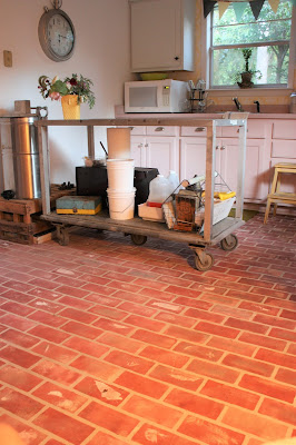 beekeeping equipment in a kitchen with faux brick floor