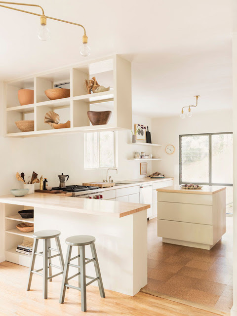neutral kitchen with white cabinets, open shelving filled with collected antique bowls, and mint bar stools
